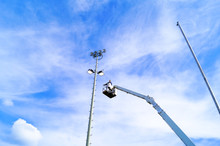Low Angle View Of Man Standing On Cherry Picker By Floodlight Against Sky