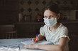 A girl in a protective mask draws with a pen in a sketchbook. Idea for quarantining a child