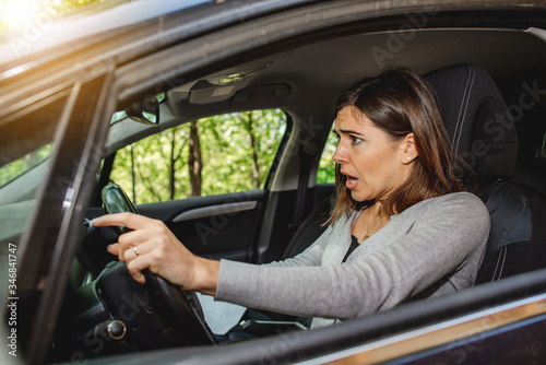 Caucasian young woman driver scared and screaming because having an abrupt braking to avoid and accident Wallpaper Mural