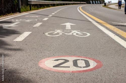 Cuadros en Lienzo bicycle and speed limit signs on asphalt path