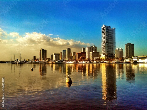 Foto Roxas Boulevard Reflected On Water Against Blue Sky