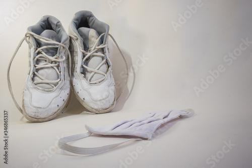 Photo Zapatillas blancas viejas y una mascarilla con un fondo blanco