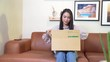 Excited young woman customer opening parcel box on sofa at home.