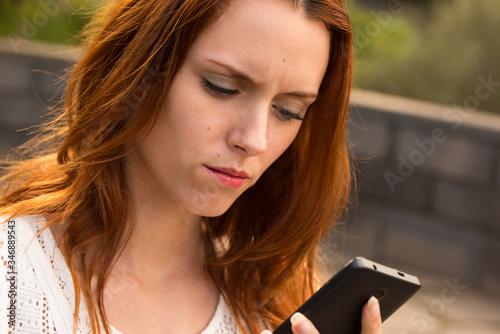 Tela Chica joven y wuapa haciendo un selfie o videoconferencia con el teléfono mobil, algo muy de moda en los millennials que estan muy conectados tecnologicamente