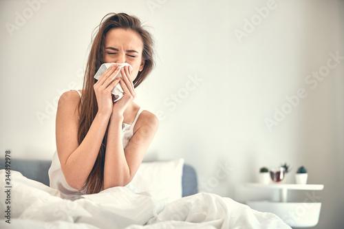 Obraz na plátně Caucasian sick lady with runny nose sitting on soft bed