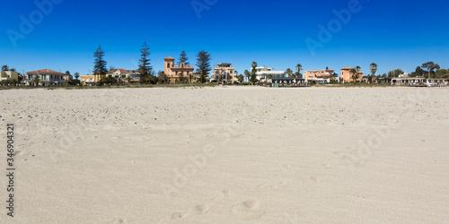 foto di un aspiaggia co centro abitato in lontananza Canvas-taulu