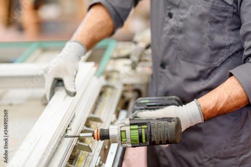 Carta da parati lavorazione industriale con un trapano elettrico da parte di u operaio