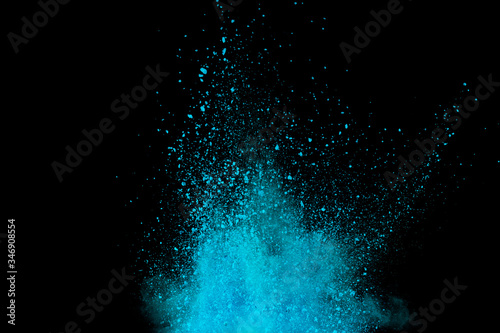 Explosion of blue, aqua and violet dust on black background.
