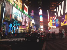 People At Times Square In Illuminated City At Night