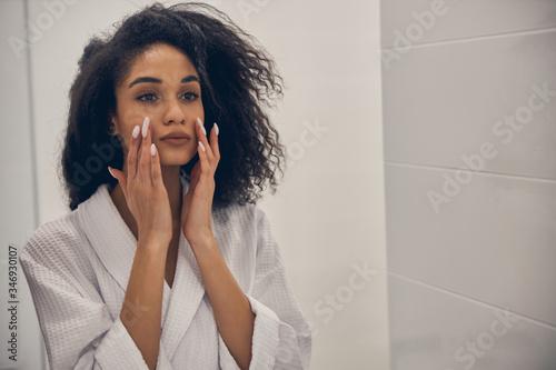 Focused woman examining the skin on her face Fototapeta
