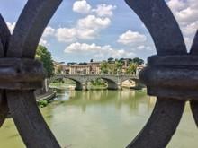 Ponte Santangelo Over Tiber River Against Sky In City Seen Through Railing