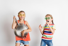 Portrait Of Happy Little Girls Pretending To Sing And Play Music