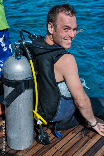 Photo Smiling young man with compressed air cylinder on his back sits on the deck