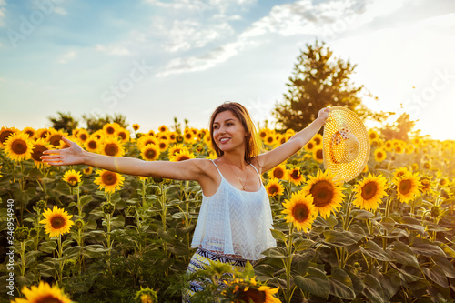 Happy free woman opened arms walking in blooming sunflower field holding straw hat. Summer vacation