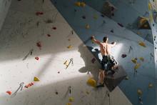 Shirtless Man Climbing On The Wall In Climbing Gym