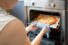 Crop View Of Woman Taking Tray With Baked Pizza Out Of Oven
