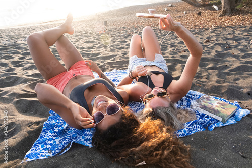 Two happy women lying on the beach listening music on the phone, Costa Rica - 346972348