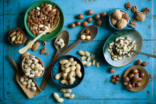 Overhead View Of Various Nuts In Bowls And On Spoons On Blue Rustic Table