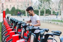 Young Man Taking A Rental Bike...