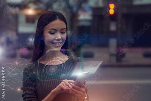 Obraz Smart city data concept. A beautiful young Asian woman is connected to a public digital network through her nod, mirrored as an augmented reality projection emerging from her phone. - fototapety do salonu