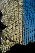 A Building Is Reflected Off Another Skycraper Glass Windows In New York
