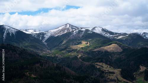Hiking on Ukrainian Montenegrin snowcapped ridge with white clouds and blue sky. Contrast background. Travel and relax