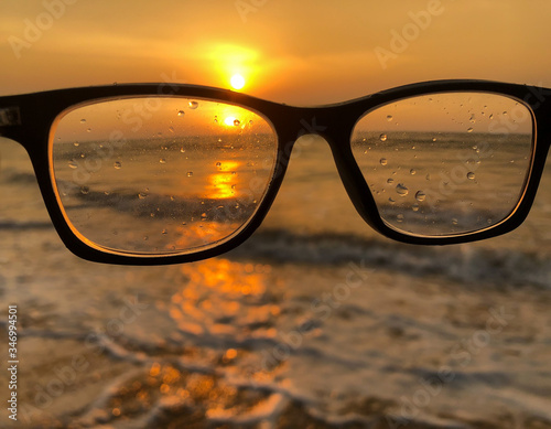 Photo A pair of glasses at the beach with the sunset and how unclear life is to a pers