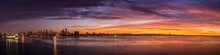 Panoramic View Of Sea By Cityscape Against Cloudy Sky During Sunset