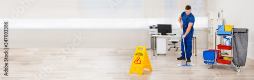 Foto Janitor Mopping Floor In Office