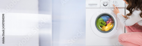 Fototapeta Woman Pressing Button Of Washing Machine obraz