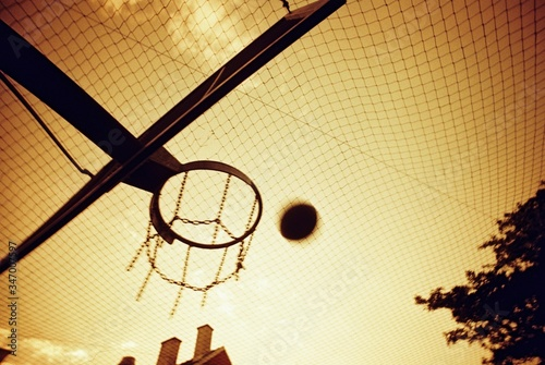 Photo Basketball Backboard And Hoop On Street In Orange Colors Of Sunset