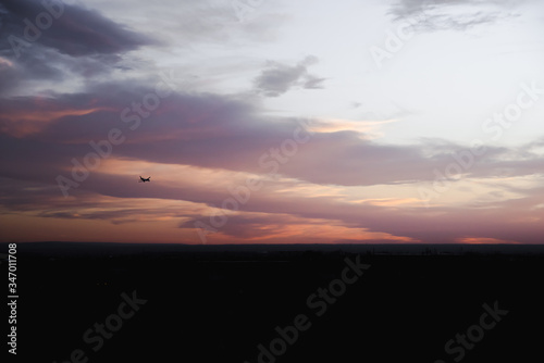 An airplane flying in a sunset sky over Albuquerque, New Mexico. Canvas Print