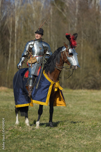 Photo Young adult man in knightly armor rides across the field on a horse in armor