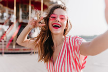 Adorable Girl In Stylish Sunglasses Posing With Inspired Face Expression Beside Carousel. Outdoor Photo Of Blissful White Woman Making Selfie In Amusement Park.