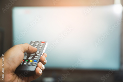 Young man holding television remote control Fototapet