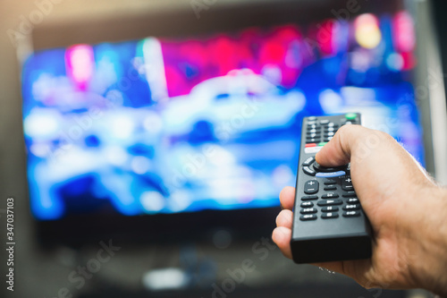 Young man holding television remote control Fototapeta