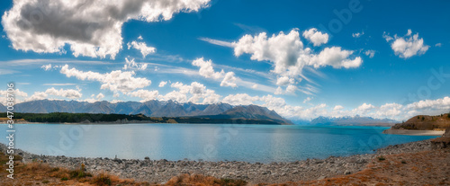 Fototapeta Lake Pukaki Panorama in Mackenzie Basin in New Zealand's South Island, famous for its distinctly milky blue color and one of the iconic destinations for tourists and filmmakers alike
