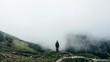 Leinwandbild Motiv Rear View Of Woman Standing On Mountain During Foggy Weather