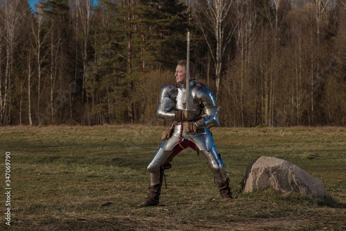 Photo A knight on foot in armor and holding a sword in his hands shows combat attacks on the battlefield