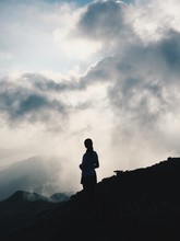 Woman Standing On Silhouette Field Against Cloudy Sky