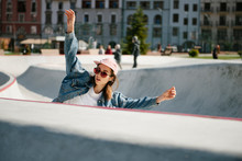 Young Woman With Raised Arms Doing Skateboarding Trick Outdoor