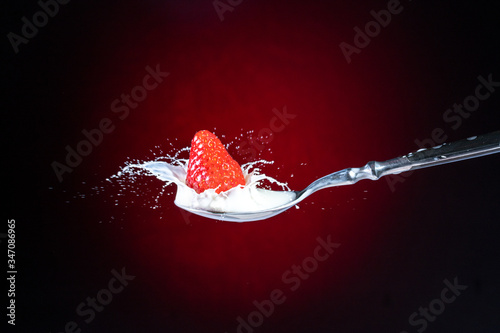Fényképezés A tasty ripe red Strawberry fall into milk in front of a gradient red backdrop o