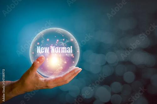 Transparent of earth with the word of new normal floating above the hand with orange and blue light on a white bokeh background and copy space Canvas Print