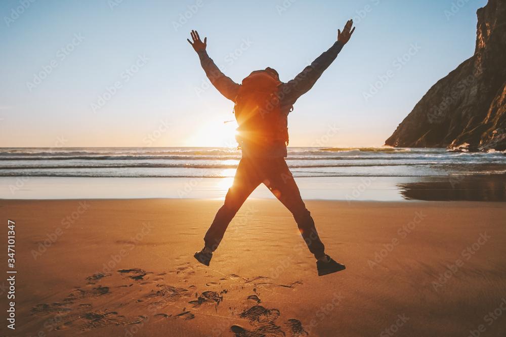 Fototapeta Man jumping on beach travel healthy lifestyle active vacations outdoor adventure success happy emotions traveler enjoying sunset ocean landscape