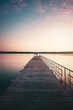 Wooden Bridge over the Lake. Fisherman on bridge at Sunset. Quiet place. Lake at sunset