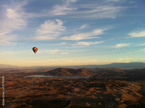 Fotografiet Hot Air Balloon Flying Over Landscape Against Sky During Sunset