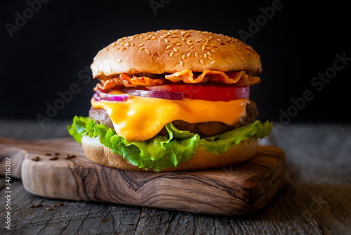 Fototapeta Burger with cheese, bacon, tomato and lettuce on dark wooden background obraz