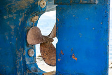 An Old Scrappy And Rusty Propeller Screwed At The Rear Of A Blue Ship Hull. Rough Blue Surface With Copy Space