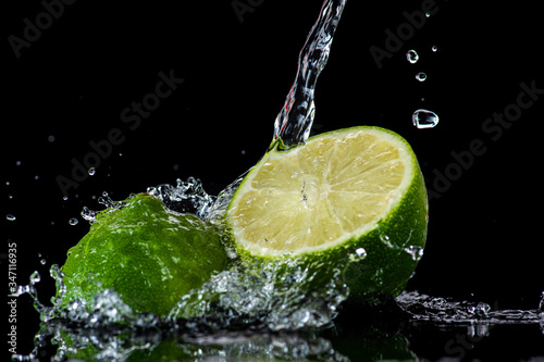 lime with splashes and streams of water on a black or white background isolated