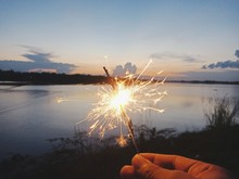 Cropped Hand Holding Burning Sparkler By Lake Against Sky At Sunset